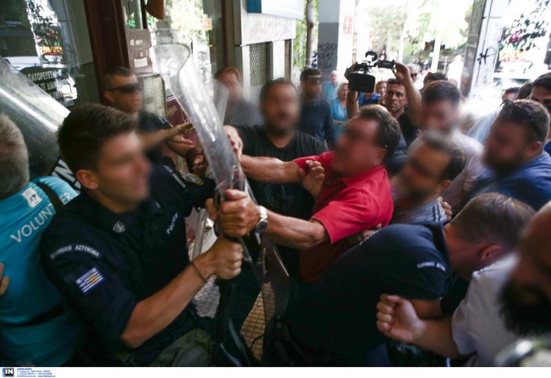 Αντρας με κόκκινη μπλούζα κρατά ασπίδα αστυνομικού