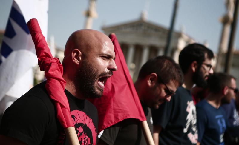 Μέλος του ΠΑΜΕ φωνάζει συνθήματα κατά τη διάρκεια της πορείας