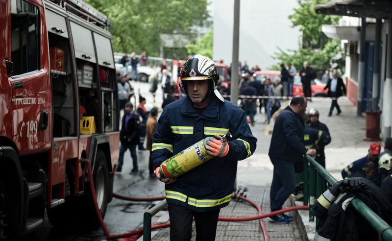 Ενας πυροσβέστης που συμμετείχε στην κατάσβεση της πυρκαγιάς στο ΑΠΘ περπατά κρατώντας στα χέρια του μια φιάλη με οξυγόνο