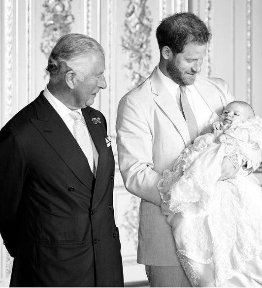 πρίγκιπας Κάρολος κοιτάζει με τρυφερότητα τον Άρτσι που τον κρατά στην αγκαλιά του ο Χάρι