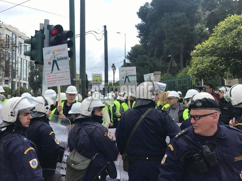 Μηχανικοί με αστυνομικές δυνάμεις μπροστά τους