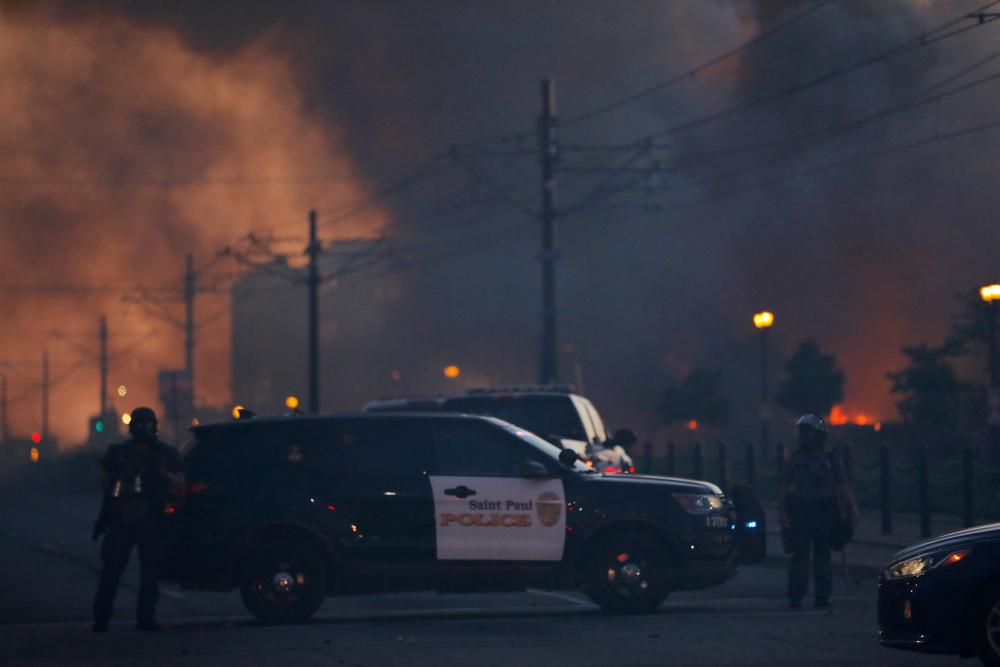 Αστυνομικοί μπροστά από όχημα με φόντο καπνούς από φωτιές