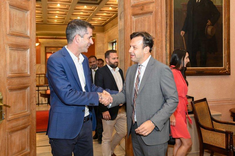 Ο Κώστας Μπακογιάνης χαιρετά τον  Γιώργο Μπρούλια στην παράδοση-παραλαβή στο δημαρχείο Αθήνας στην πλατεία Κοτζιά