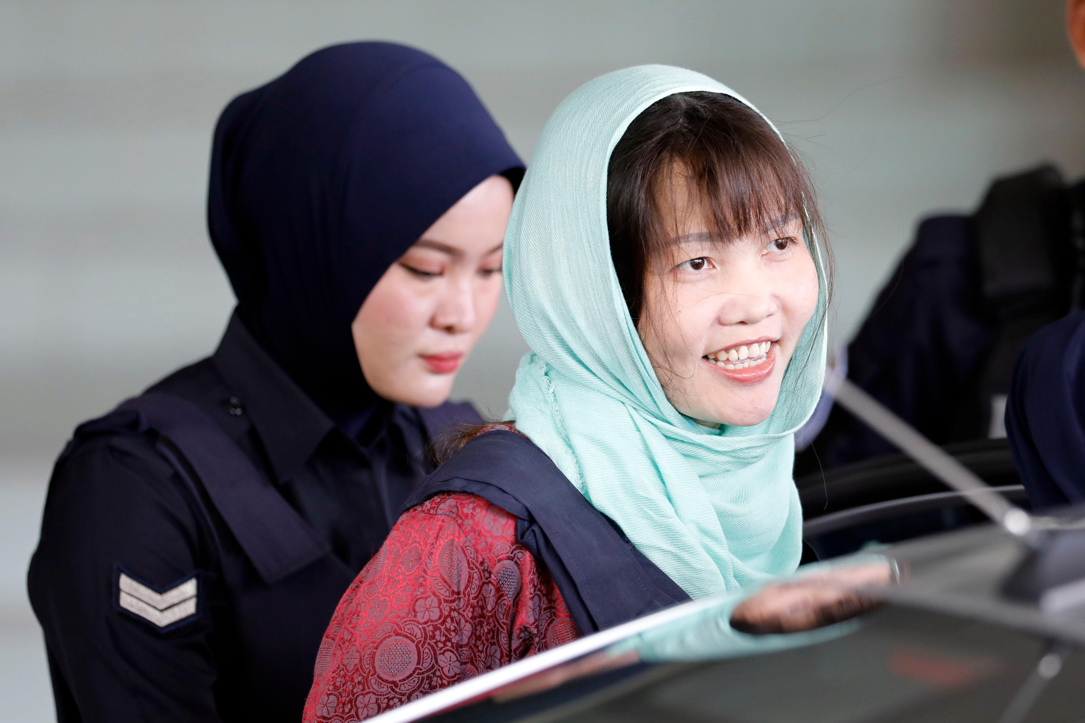 Βιετναμέζα με μαντήλα στο κεφάλι οδηγείται από γυναίκα αστυνομικό