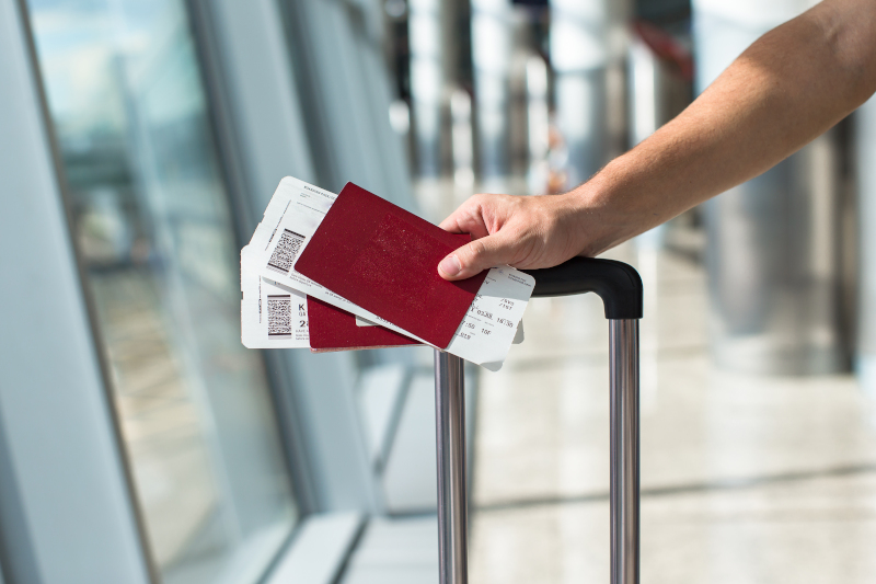 Άνδρας κρατά κάρτα επιβίβασης και διαβατήριο