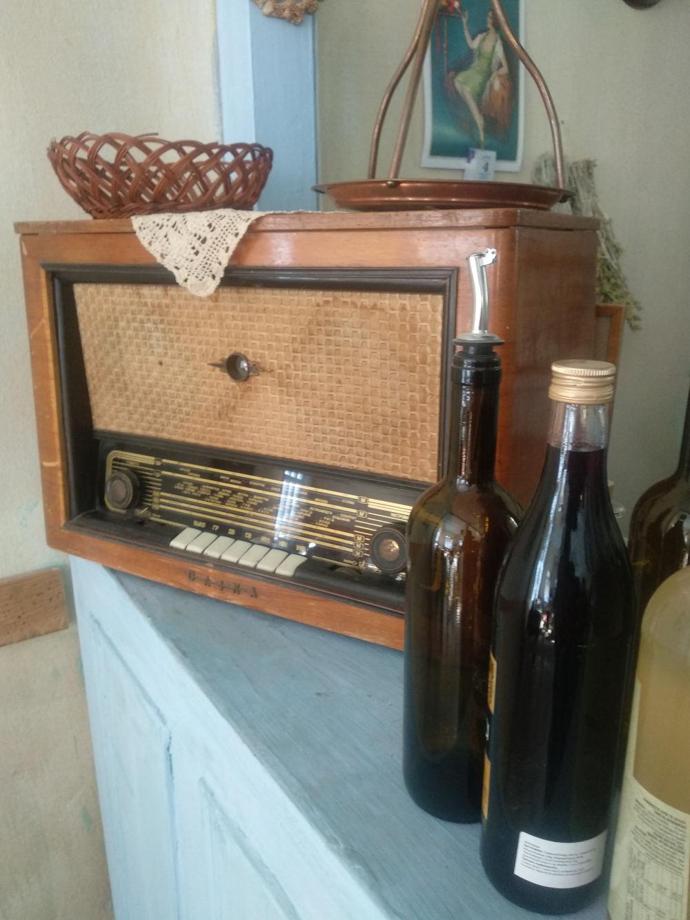 Το ξύλινο ραδιόφωνο στην άκρη του πάγκου του καφενείου. Το μόνο κτίριο που διαθέτει εσωτερικούς χώρους πίσω από τα εντυπωσιακά σκηνικά της σειράς «Άγριες Μέλισσες»