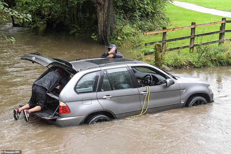 Εικόνα πλημυρισμένων δρόμων έξω από το Μπέρμιγκχαμ με τον οδηγό να προπσπαθεί να γλιτώσει από τα ρομητικά νερά