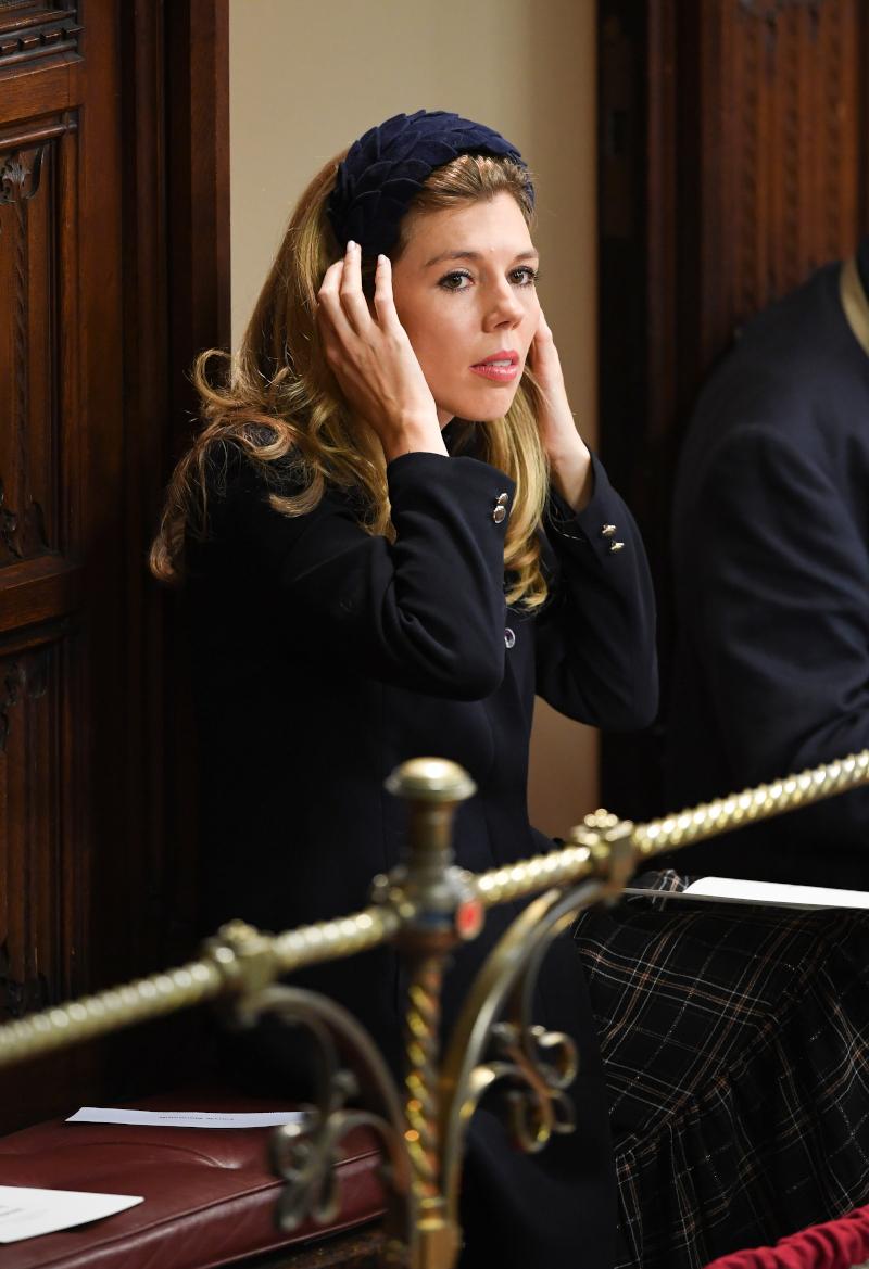 Η Κάρι Σίμοντς με καρό σκούρο φόρεμα και μπλε στέκα στη βουλή