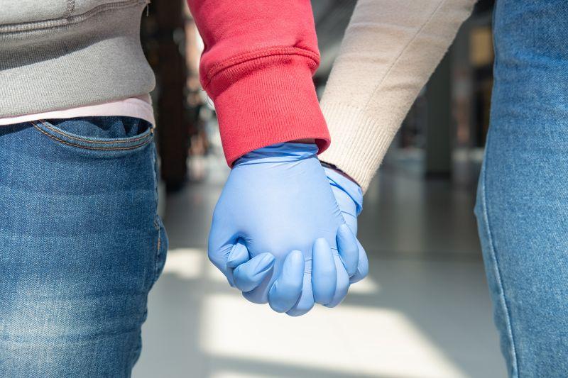 ζευγάρι κρατιέται χέρι χέρι φορώντας γάντια
