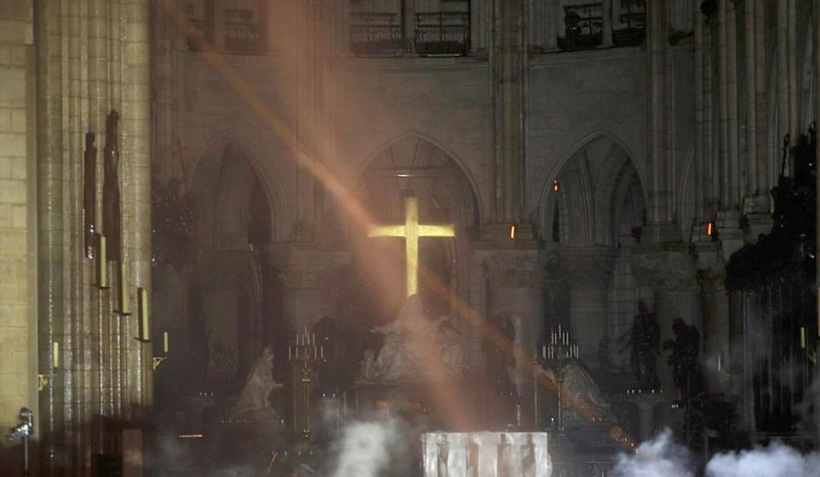 Ο μεγάλος κίτρινος σταυρός φωτισμένος από τις φλόγες μέσα στους πυκνούς καπνούς στο εσωτερικό της Παναγίας των Παρισίων.
