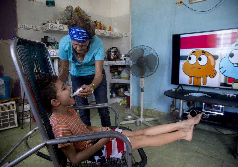 Κουβανή δίνει σταγόνες φαρμάκου σε παιδί για την πρόληψη από τον κορωνοϊό