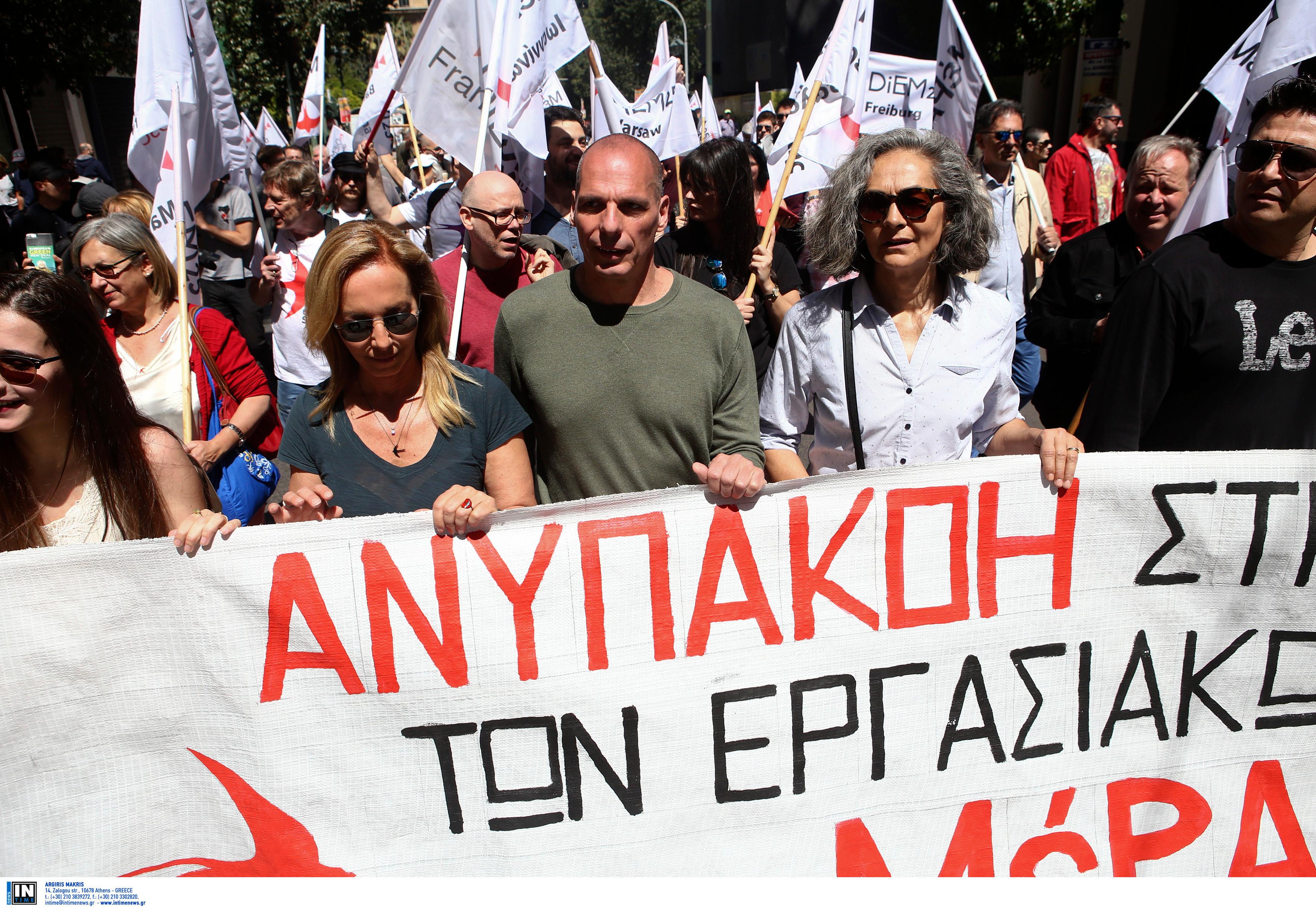 Δανάη Στράτου και Γιάνης Βαρουφάκης στην πορεία, κρατώντας πανό
