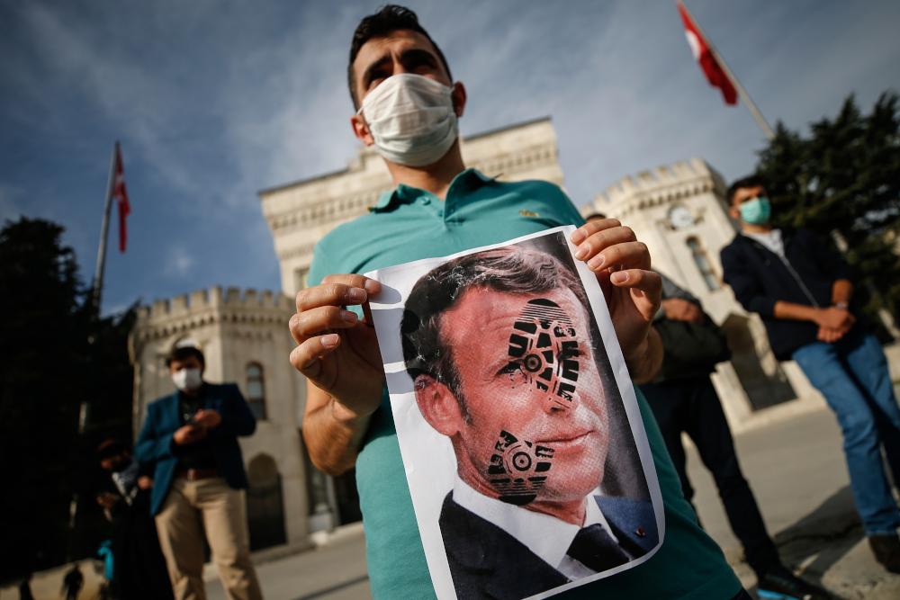 Τούρκος διαδηλωτής με αφίσα Μακρόν και πατημασιά