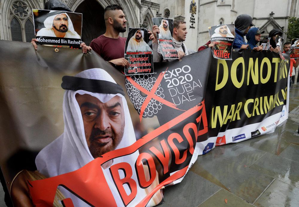 Πλακάτ με το σύνθημα «Χορηγός της πορνείας και της δουλείας», κάτω από μια φωτογραφία του εμίρη κρατούσαν διαδηλωτές έξω από  το δικαστήριο