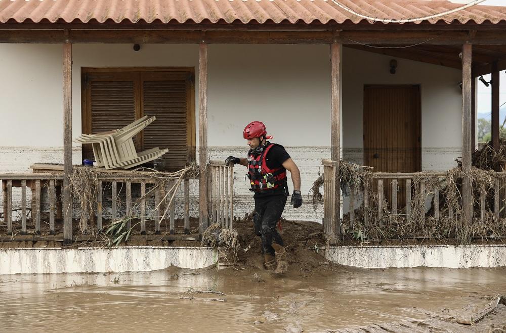 Διασώστης έξω από πλημμυρισμένο σπίτι