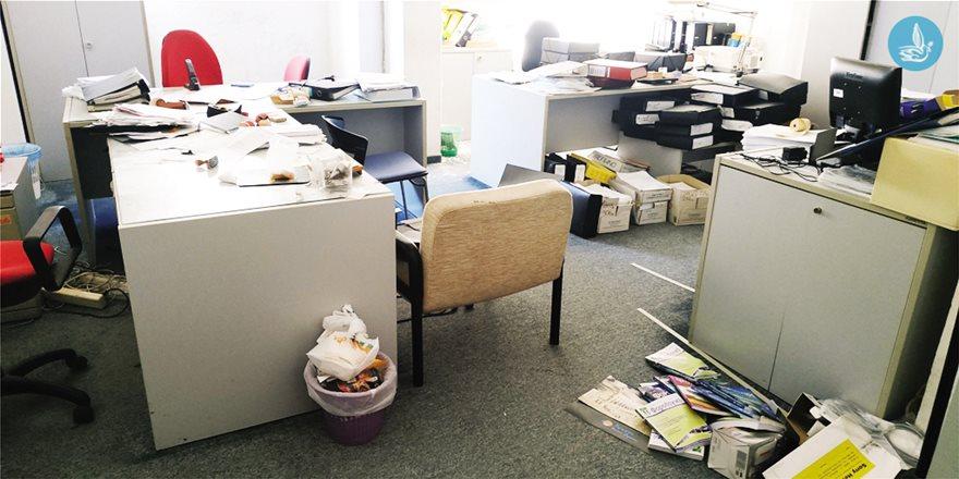 Γραφεία με πληθώρα εγγράφων πεταμένα στο πάτωμα