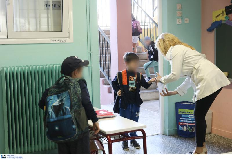 Δασκάλα βάζει αντισηπτικό σε μαθητή