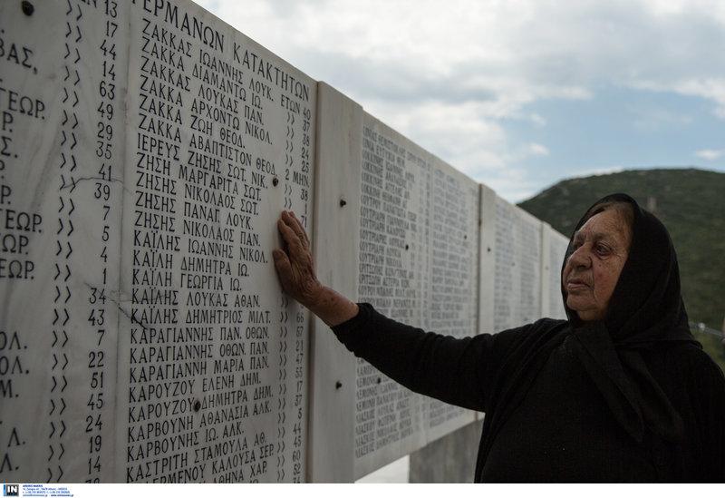 Μια ηλικιωμένη μαυροφορεμένη γυναίκα στη μαρμάρινη στήλη με τα ονόματα των θυμάτων στο Δίστομο
