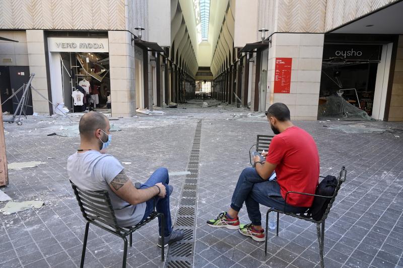 Δύο άνδρες καθισμένοι σε εμπορικό της Βηρυτού