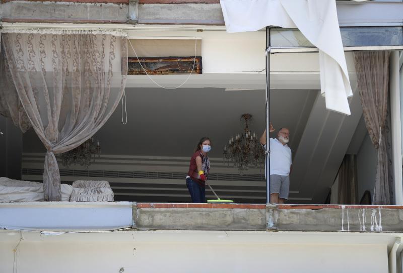 Ανθρωποι στέκονται σε κατεστραμμένο σπίτι στη Βηρυτό