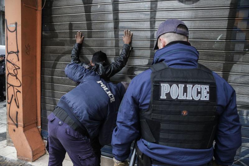 Αστυνομικοί κάνουν σωματικό έλεγχο άνδρα