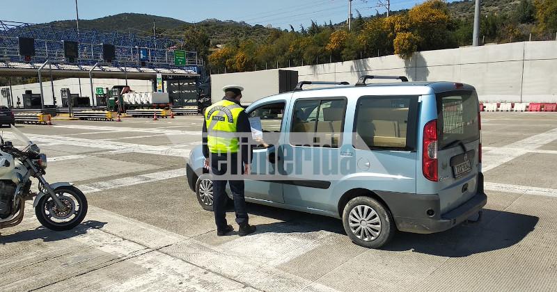 Αστυνομικός διενεργεί έλεγχο στα διόδια της Ελευσίνας λόγω των μέτρων για τον κορωνοϊό