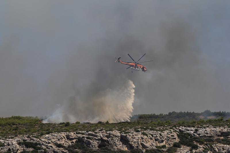 Ελικόπτερο ρίχνει νερό πάνω από φωτιά στο Λαύριο