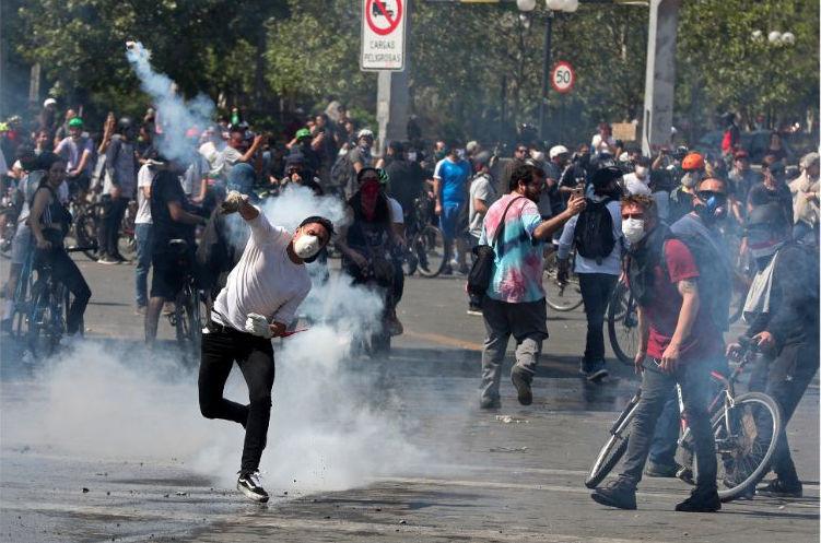 Διαδηλωτές με μάσκες σε δρόμους της πόλης της Χιλής