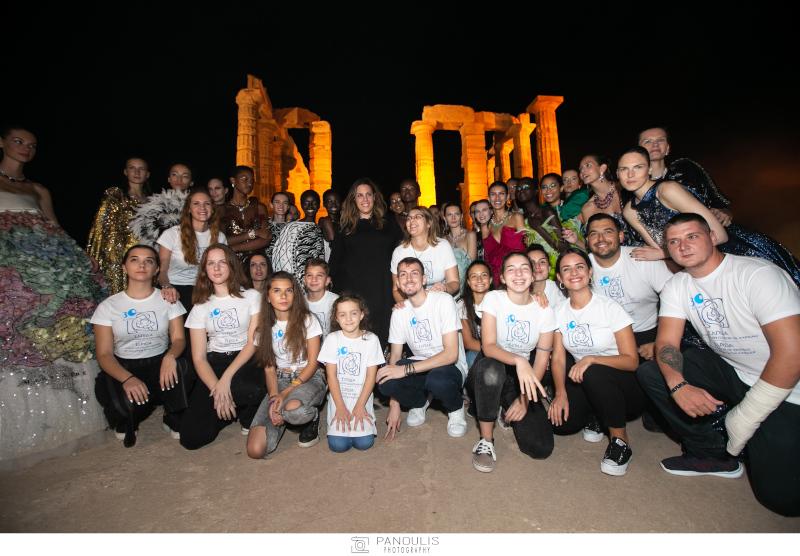 Τα παιδιά του Συλλόγου «Ελπίδα» και τα μοντέλα με την κολεξιόν της Μαίρης Κατράντζου με φόντο τον ναό του Ποσειδώνα