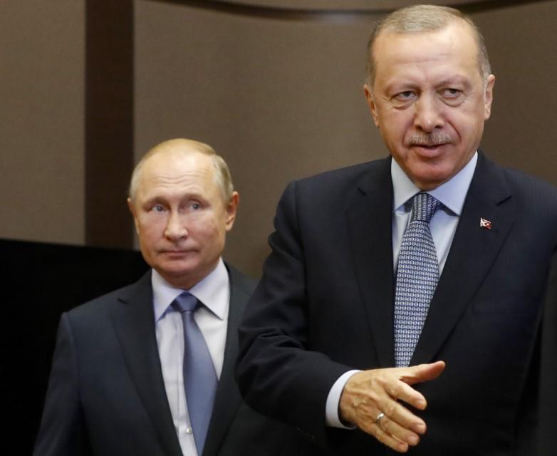 Ο Τούρκος πρόεδρος Ερντογάν τείνει το χέρι να χαιρετήσει κάποιον υπό το βλέμμα του Βλαντιμίρ Πούτιν