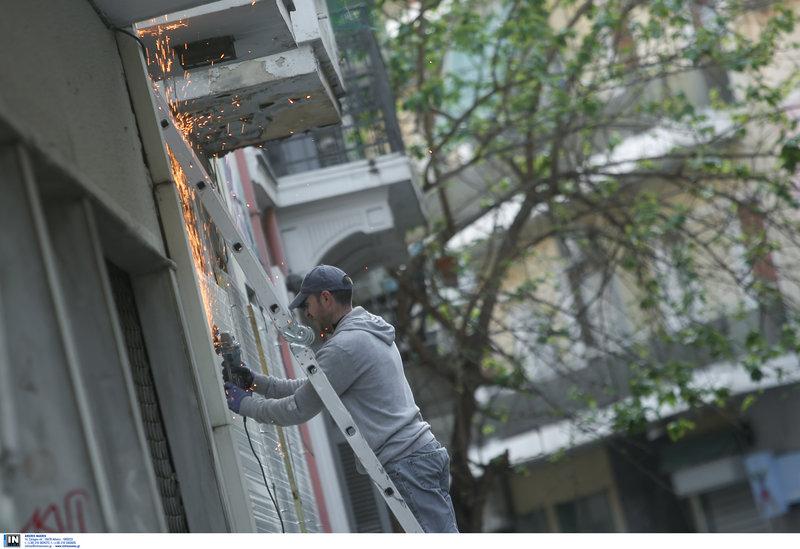 Εργάτης σφραγίζει τα κτίρια μετά την απομάκρυνση των καταληψιών