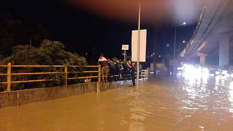 Πυροσβέστες κοιτάζουν κάτω σε δρόμο πλημμυρισμένο