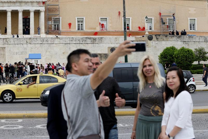 Βγάζουν selfie και γελάνε οι τουρίστες με την εικόνα ντροπής της Βουλής