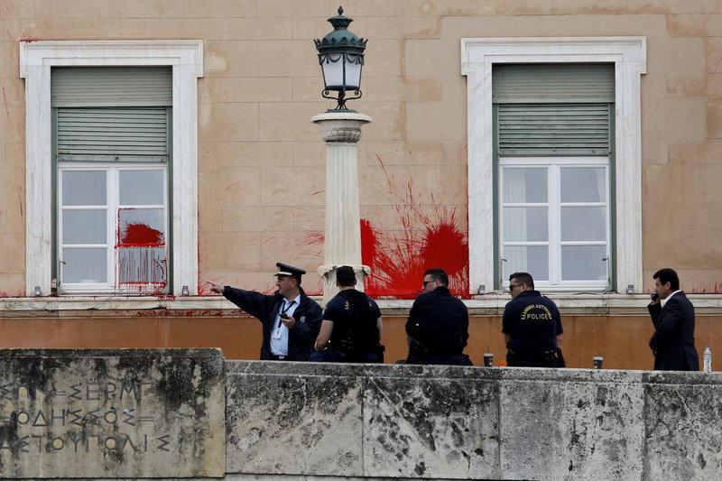 Αστυνομικός προφανώς δείχνει στους υφισταμένους του τι θα πρέπει να προσέχουν , στο βάθος η «πληγωμένη» Βουλή