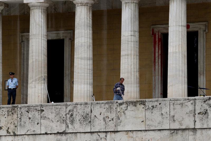 Με μία σφουγγαρίστρα στο χέρι υπάλληλος καθαρίζει τα σκαλιά στη Βουλή