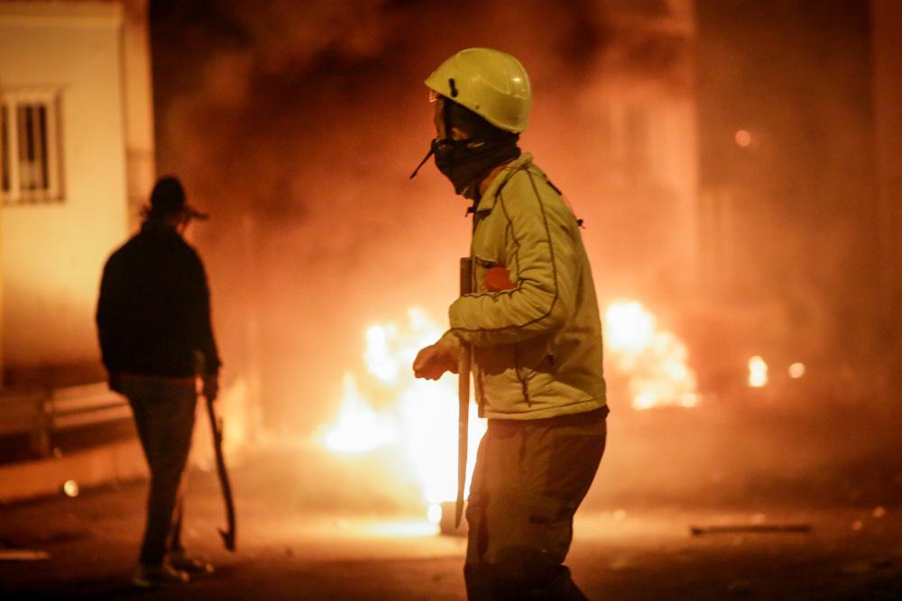 Ανδρας κρατάει λοστάρι με φωτιές στο βάθος