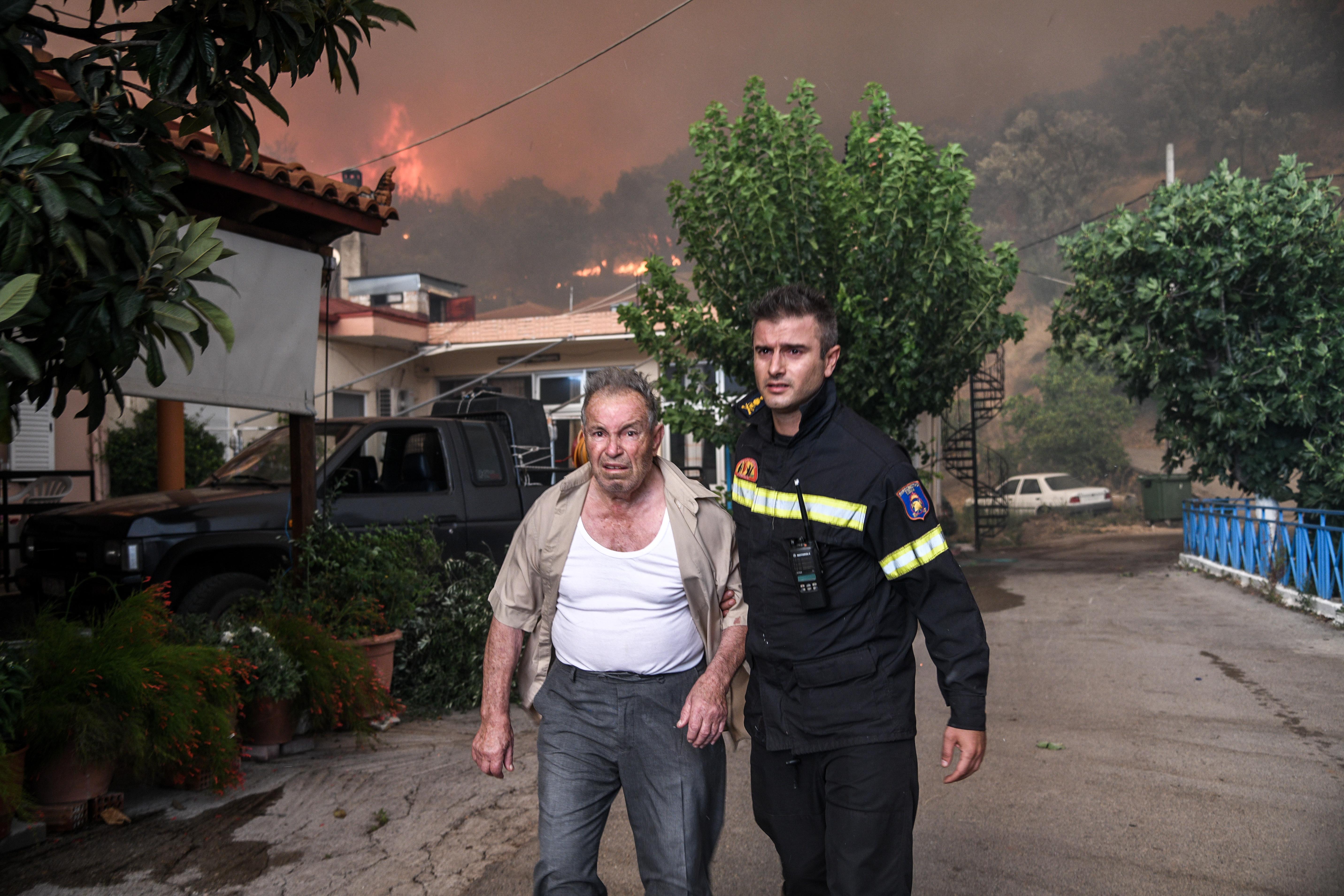 Πυροσβέστης συνοδεύει κάτοικο του χωριού Κοντοδεσπότι κατά τη διάρκεια της εκκένωσης