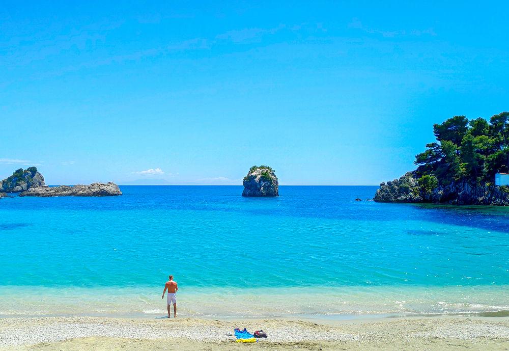 Άνδρας σε παραλία με γαλαζοπράσινα νερά και βράχους στο νερό στην Πρέβεζα
