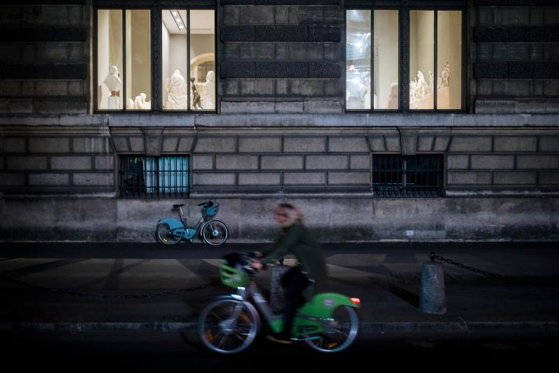 Γυναίκα με ποδήλατο έξω από το μουσείου του Λούβρου