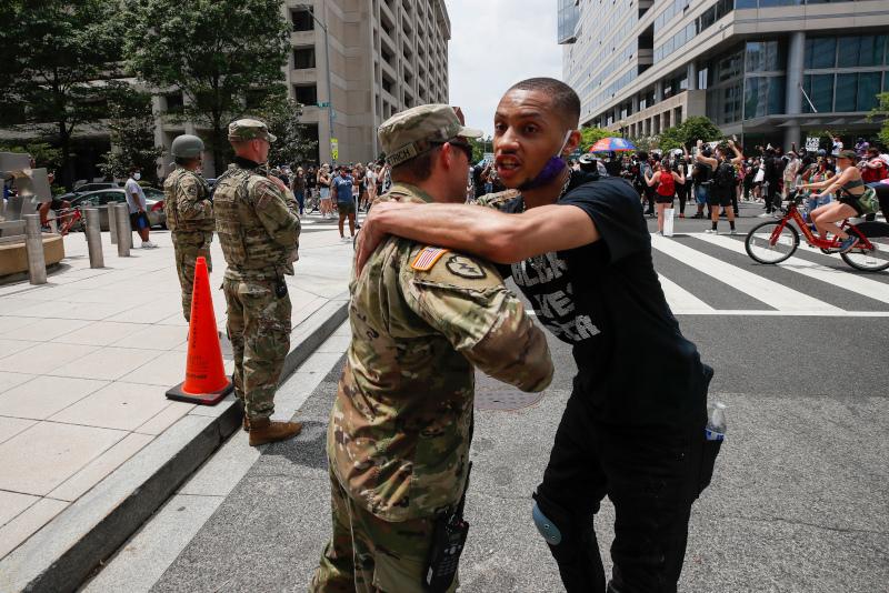 Διαδηλωτής αγκαλιάζει μέλος της Εθνοφρουράς