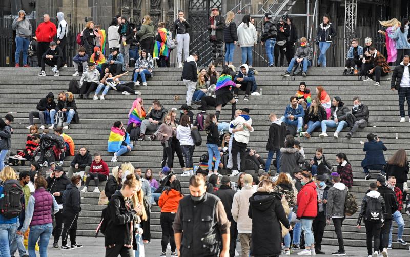 Νέοι κάθονται στα σκαλιά, με την απαιτούμενη απόσταση, στον Καθεδρικό Ναό στην Κολονία
