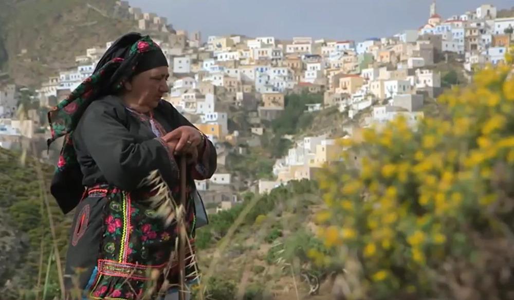 Ηλικιωμένη με παραδοσιακή φορεσιά με φόντο το χωριό της Ολύμπου
