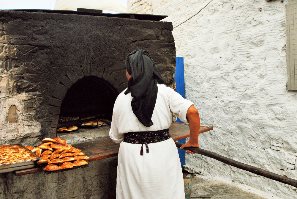Γιαγιά ψήνει ψωμί σε παραδοσιακό υπαίθριο ξυλόφουρνο στο χωριό Ολυμπος