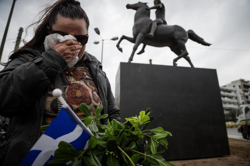 Μια γυναίκα κλαίει, κρατώντας μαντήλι στο ένα χέρι, λουλούδια και σημαία στο άλλο