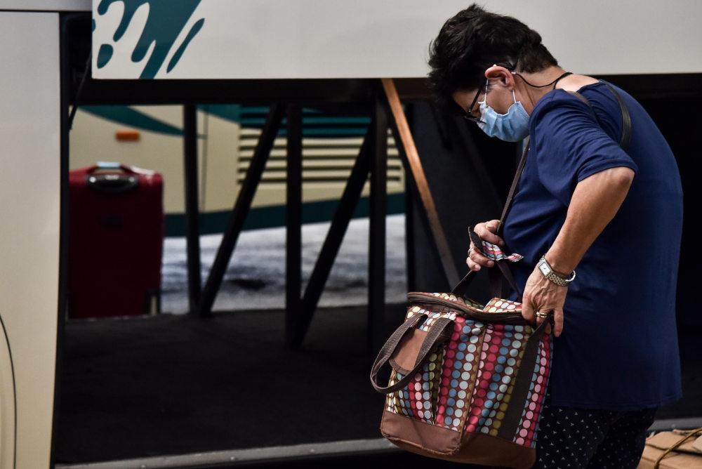 Γυναίκα τοποθετεί τις αποσκευές της σε λεωφορείο των ΚΤΕΛ