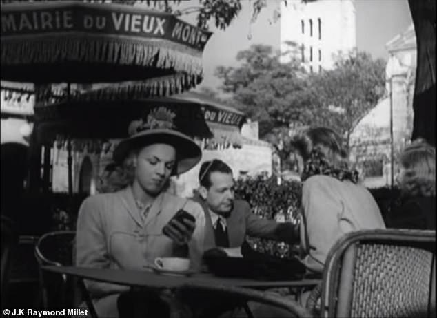 Μια γυναίκα που κάθεται μόνη, βγάζει τη φορητή συσκευή από την τσάντα της