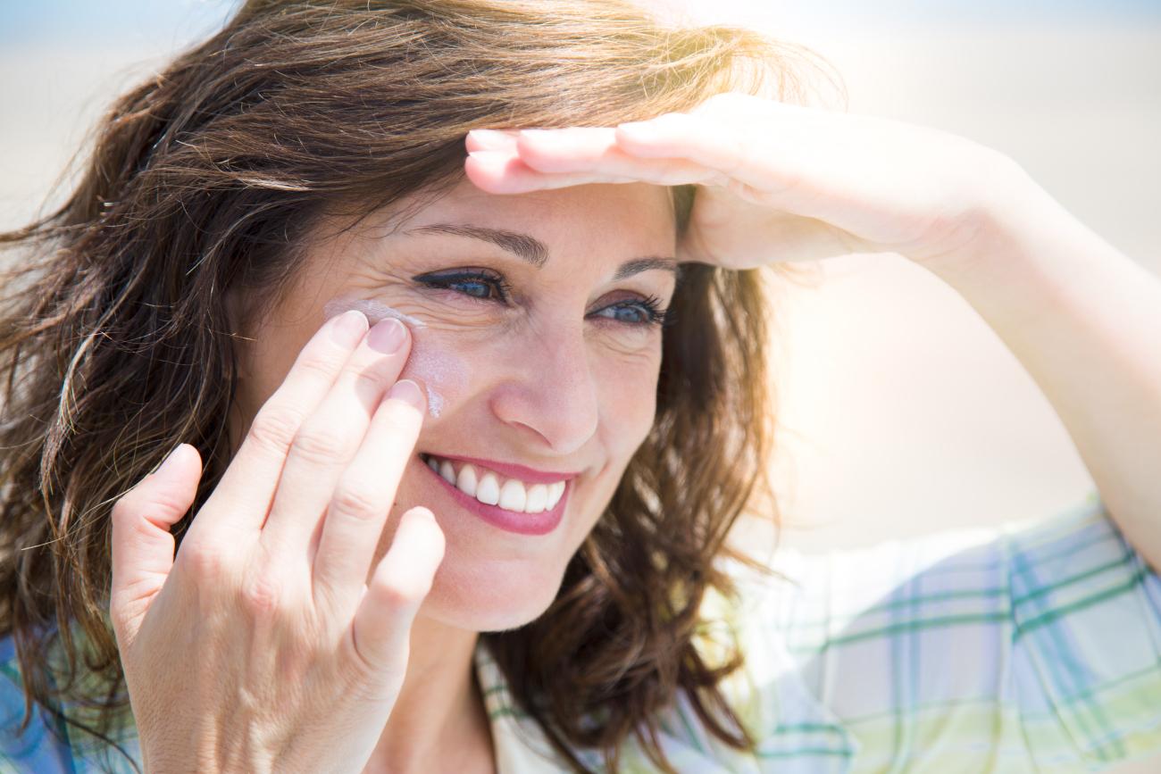 Γυναίκα βάζει αντηλιακό στο πρόσωπο