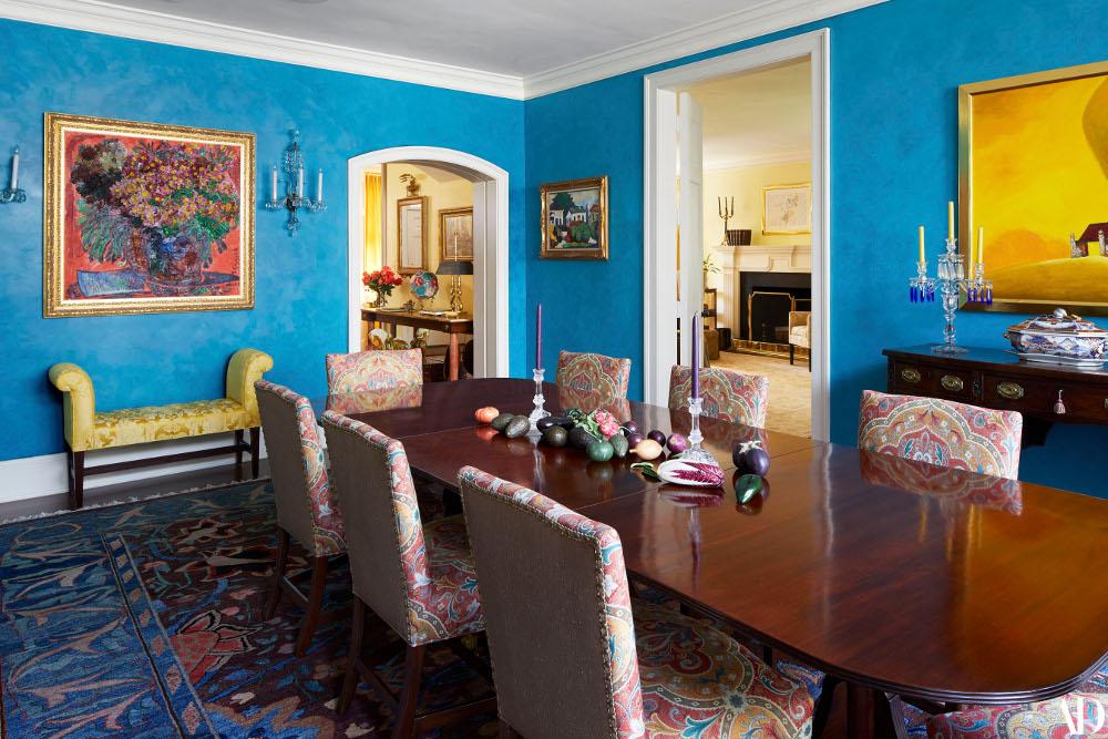 Η τραπεζαρία του σπιτιού με το έντονο μπλε χρώμα στους τοίχους και το πολύχρωμο χαλί