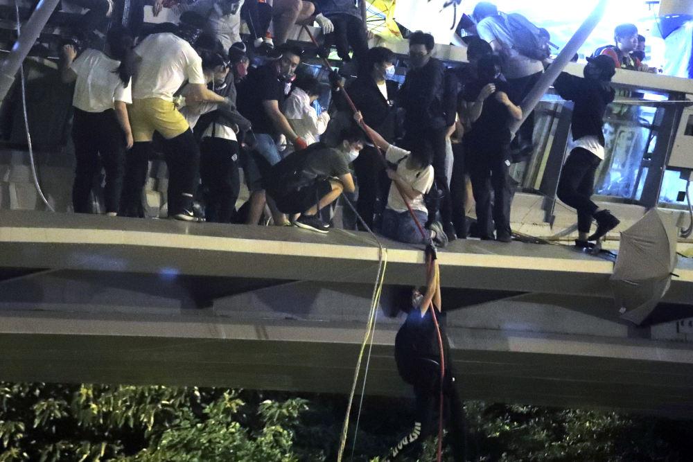 Με σχοινιά κατεβαίνουν οι διαδηλωτές από πεζογέφυρα προκειμένου να διαφύγουν της σύλληψης στο Χονγκ Κονγκ