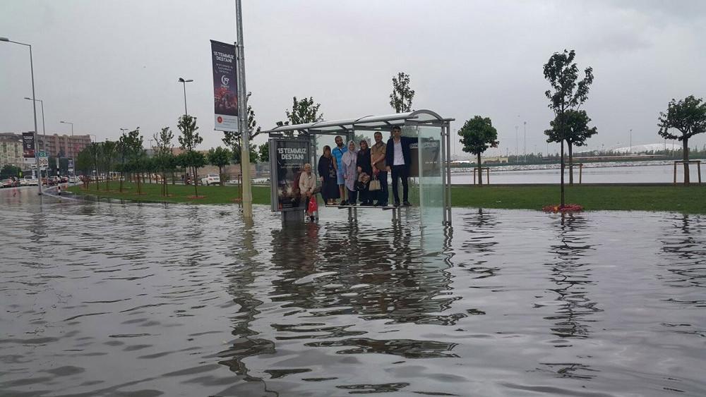 Επιβάτες λεωφορείου περιμένουν επάνω σε στάση λόγω των πλημμυρισμένων δρόμων